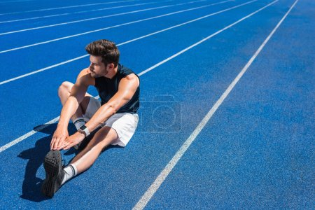 Photo for Handsome young man stretching on running track - Royalty Free Image