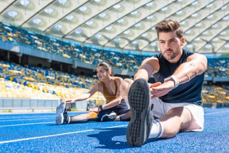 young fit couple sitting on running track and stretching at sports stadium