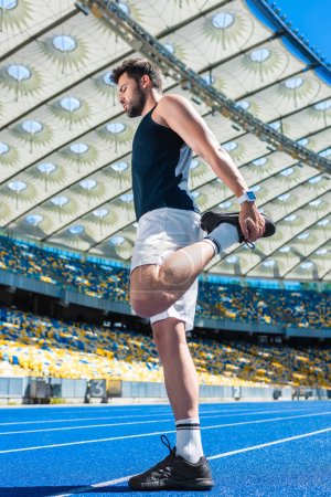 bottom view of handsome young man stretching on running track at sports stadium