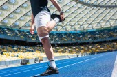cropped shot of man stretching on running track at sports stadium