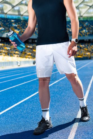 cropped shot of sportsman with water bottle at sports stadium