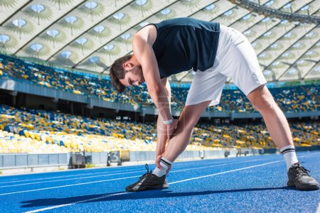 handsome young man stretching on running track at sports stadium