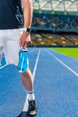 cropped shot of sportsman with water bottle on running track at sports stadium