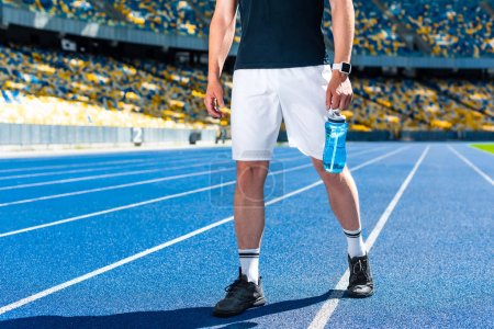 cropped shot of sportsman with fitness water bottle at sports stadium