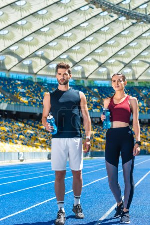 young sportive couple with bottles of water standing on running track at sports stadium