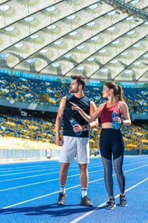 young fit couple with bottles of water chatting on running track at sports stadium