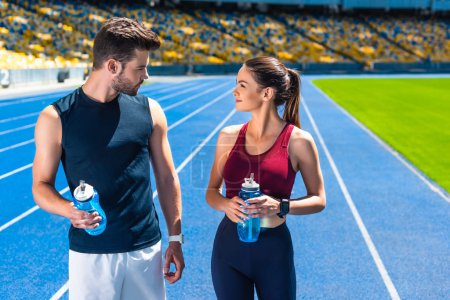 young sportive couple with bottles of water chatting on running track at sports stadium