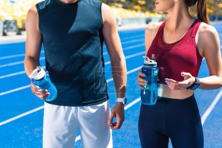 cropped shot of fit couple with bottles of water on running track at sports stadium
