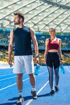 young sportive couple with bottles of water relaxing on running track at sports stadium