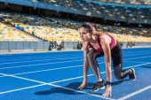 fit female runner in start position on running track at sports stadium
