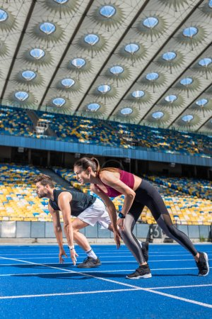 fit young male and female sprinters in start position on running track at sports stadium