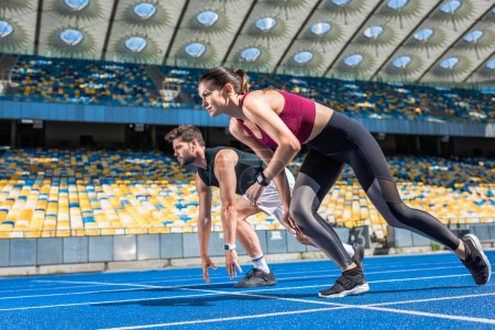 athletic young male and female sprinters in start position on running track at sports stadium