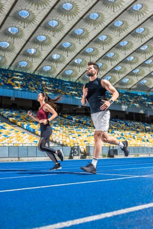 Photo for Athletic young male and female joggers running on track at sports stadium - Royalty Free Image