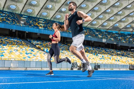 motion shot of young male and female joggers running on track at sports stadium