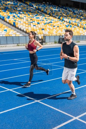 attractive young male and female joggers running on track at sports stadium
