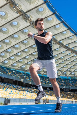 bottom view of athletic young man exercising on running track at sports stadium