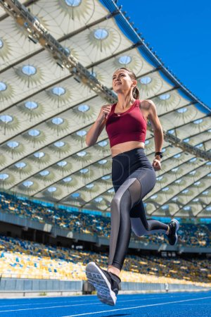 bottom view of attractive young woman running on track at sports stadium