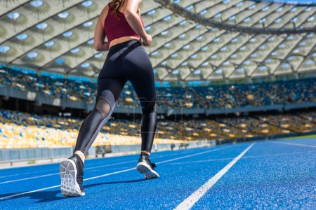 Photo for Bottom view of athletic young woman running on track at sports stadium - Royalty Free Image