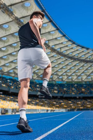 rear view of athletic young man exercising on running track at sports stadium