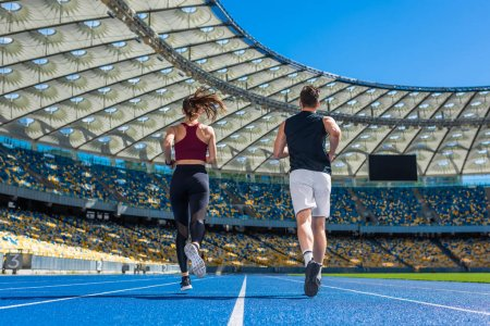 rear view of male and female joggers running on track at sports stadium