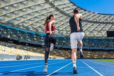 Rückansicht junger Joggerinnen und Jogger, die am Sportstadion auf der Strecke laufen