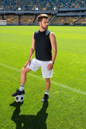 serious young soccer player standing at sports stadium with ball