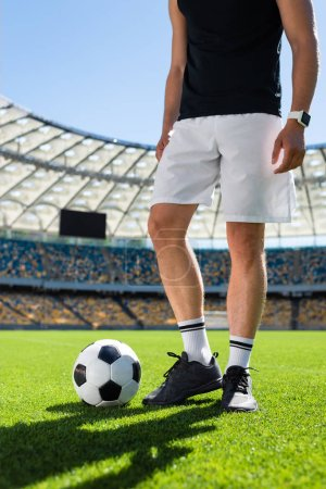 cropped shot of soccer player standing with ball at modern sports stadium