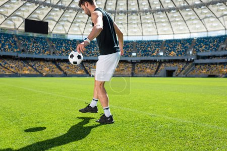 handsome young soccer player bouncing ball on leg at sports stadium