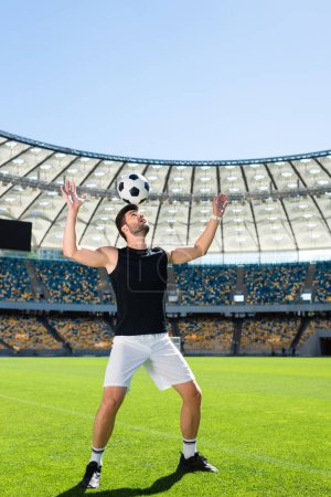 handsome young soccer player balancing ball on head at sports stadium