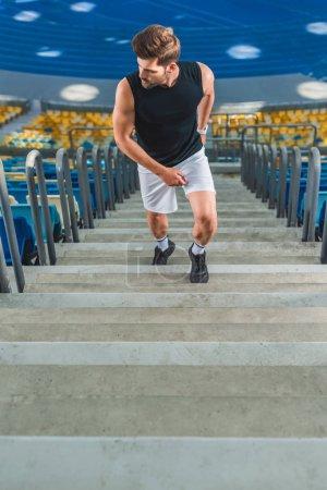 cropped shot of sportsman jogging upstairs at sports stadium