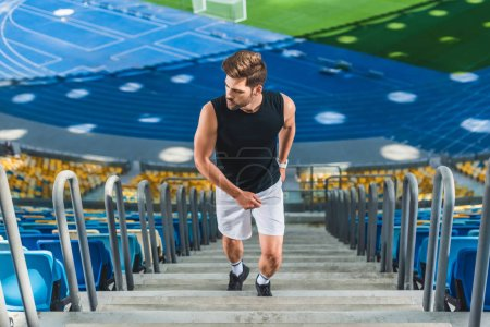 high angle view of sportive young man jogging upstairs at sports stadium