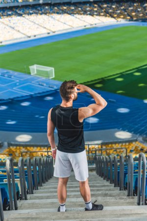 high angle view of handsome young sportsman standing on stairs at sports stadium and looking away