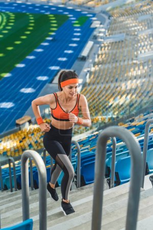high angle view of sporty young woman jogging upstairs at sports stadium