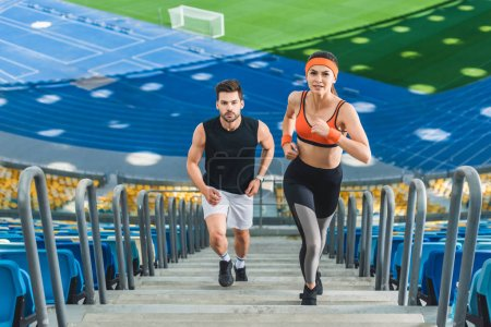 high angle view of young fit couple jogging upstairs at sports stadium