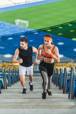 high angle view of young sportive couple jogging upstairs at sports stadium