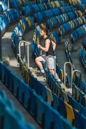 side view of attractive young man jogging upstairs at sports stadium