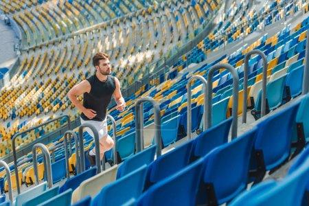 Photo pour Fit le jeune homme, faire du jogging à l'étage au stade - image libre de droit