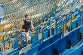fit young man jogging upstairs at sports stadium