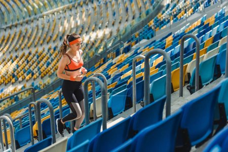 Photo for High angle view of beautiful fit woman jogging upstairs at sports stadium - Royalty Free Image