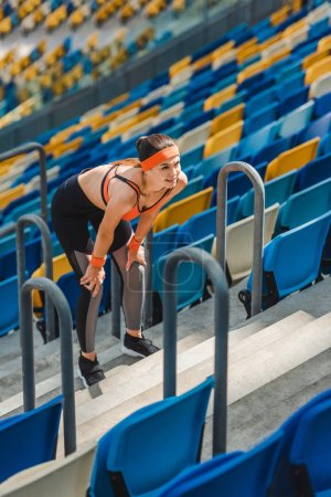 high angle view of tired young woman relaxing on stairs at sports stadium
