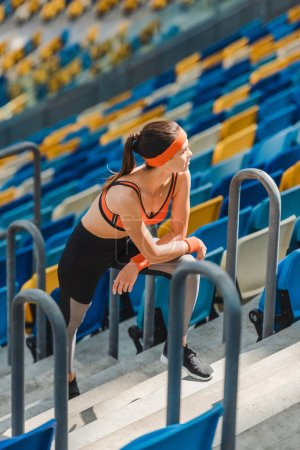high angle view of exhausted sportive woman relaxing on stairs at sports stadium