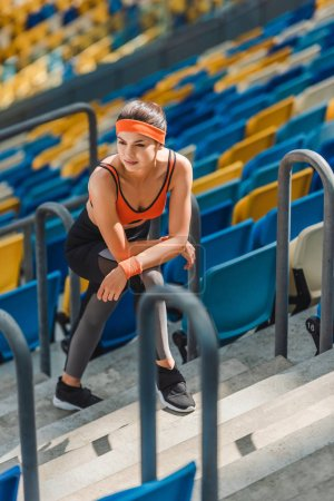 high angle view of exhausted athletic woman relaxing on stairs at sports stadium