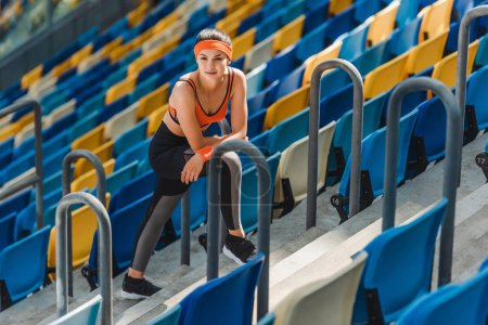 high angle view of exhausted fit woman relaxing on stairs at sports stadium