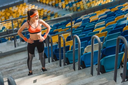 high angle view of sportive young woman standing on stairs at sports stadium with arms akimbo