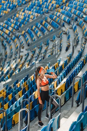 high angle view of beautiful young woman drinking water while standing on stairs at sports stadium