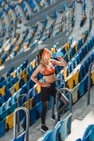 high angle view of happy young woman drinking water on tribunes at sports stadium