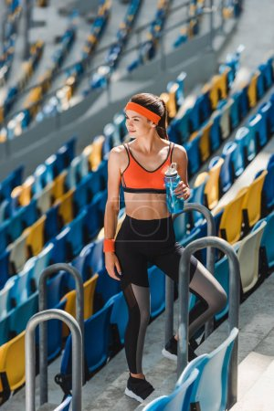 high angle view of happy young woman with water bottle standing on tribunes at sports stadium