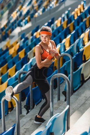 high angle view of sporty young woman stretching on tribunes at sports stadium
