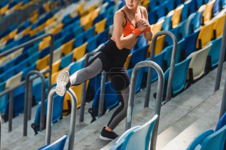 high angle view of fit young woman stretching on tribunes at sports stadium