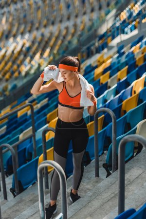 high angle view of exhausted young woman with towel at sports stadium